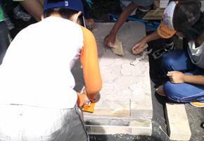 耐火レンガに粘土を塗っているところ