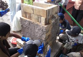 積み上げた耐火レンガに粘土をつけているところ
